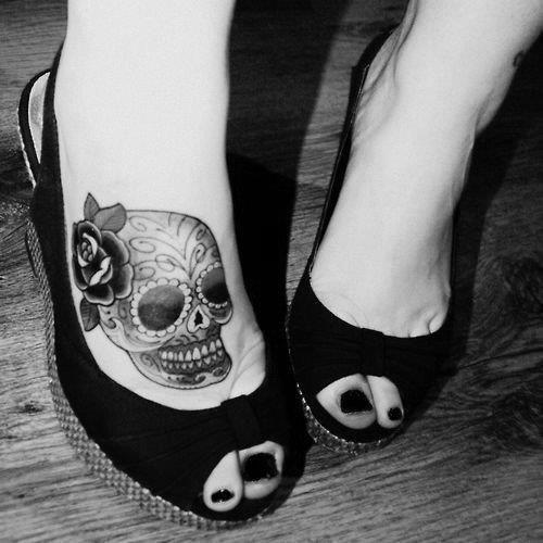 Un tatouage d'une crane sur le pied