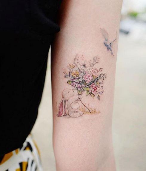 Tatouage de bras de lapin avec des fleurs