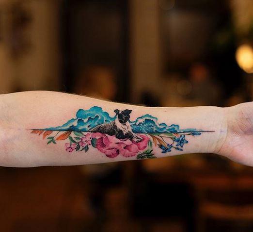 Chien dans un tatouage floral de l'avant-bras