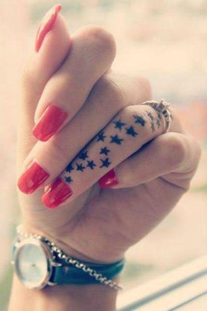 Exemple de tatouage d'annulaire recouvert de petites étoiles noires