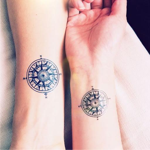 Même motif de tatouage de femme rose des vents tatoué sur 2 personnes