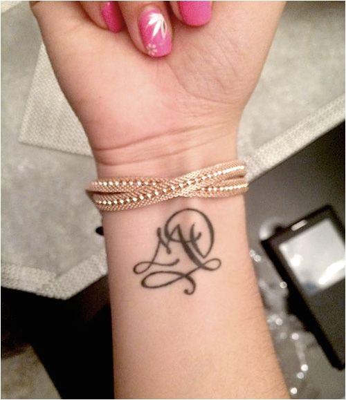 Conception de tatouage deux lettres entrelacées pour un poignet